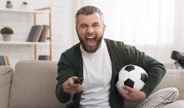 Emotional man watching football game on TV - Stock Photo - Images