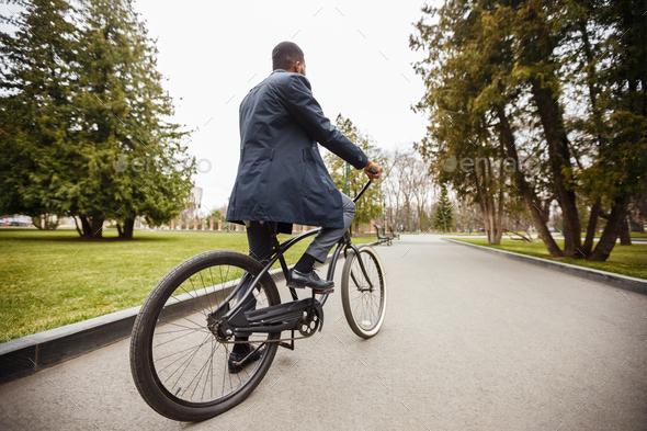 Businessman riding bicycle, going to work through autumn park - Stock Photo - Images