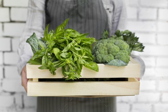 Woman holding Organic and eco green vegetables inside box - Stock Photo - Images