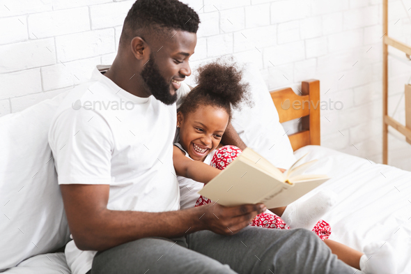 Loving african american dad reading fairy tales to his little daughter - Stock Photo - Images