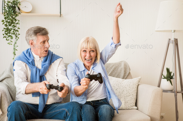 Senior couple having great time, playing video games - Stock Photo - Images