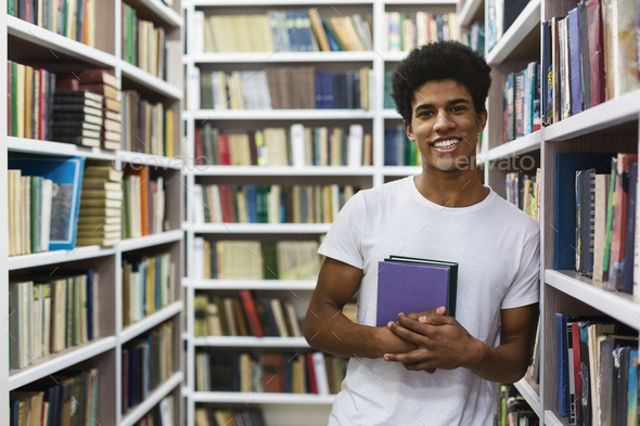 Cheerful african american guy staying between bookshelves, holding book - Stock Photo - Images