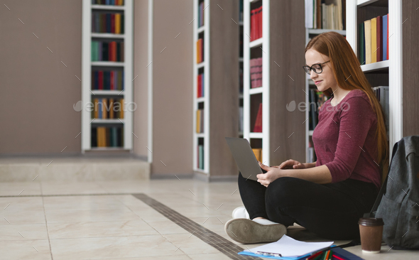Young female student doing homework, sitting on floor - Stock Photo - Images