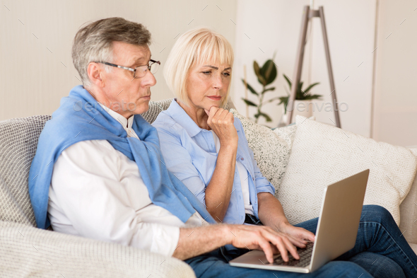 Senior couple reading news on laptop at home - Stock Photo - Images