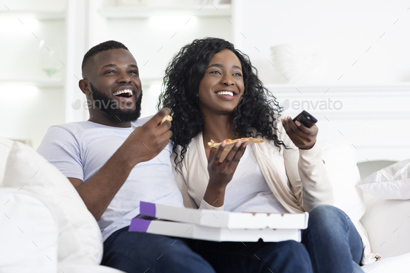 Lovely black couple sharing pizza and watching tv at home - Stock Photo - Images