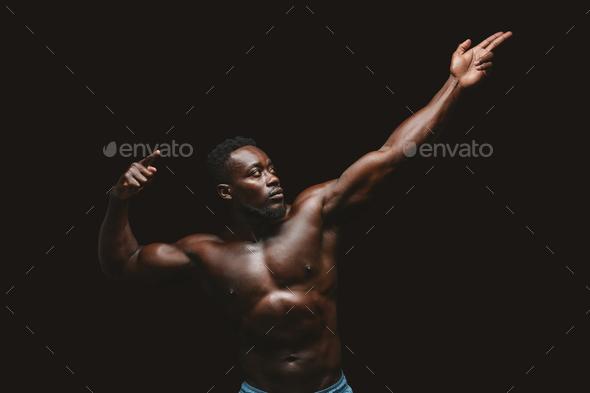 Artistic black bodybuilder posing over black background - Stock Photo - Images