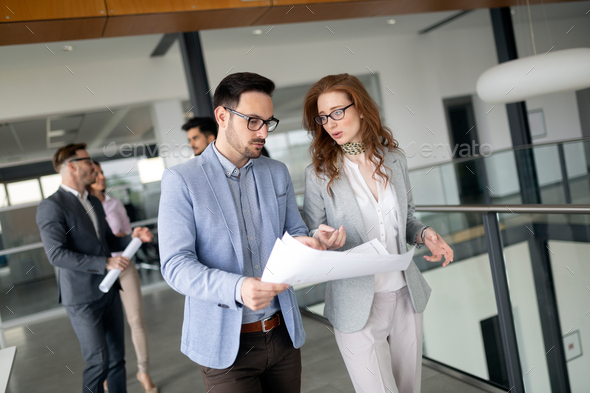 Confident business people reviewing project in office - Stock Photo - Images