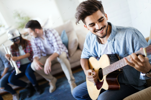 Friends at home enjoying singing and playing guitar - Stock Photo - Images