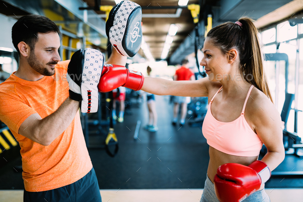 Picture of woman wearing boxing gloves in gym - Stock Photo - Images