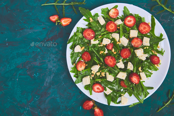 Fresh salad with arugula, strawberries, feta cheese and nuts. - Stock Photo - Images