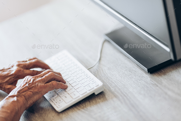 Elderly woman typing on a keyboard - Stock Photo - Images