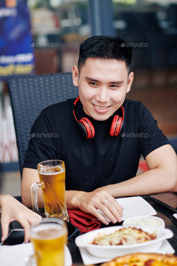Asian man sitting in cafe - Stock Photo - Images