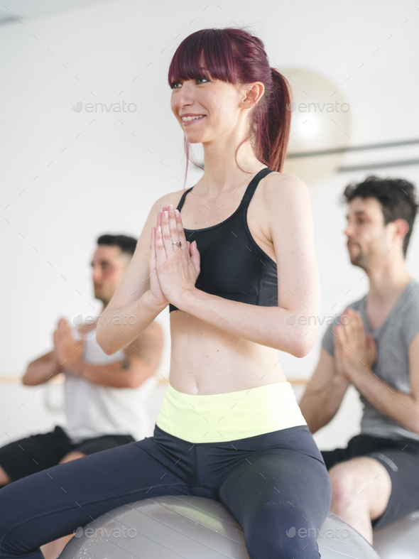 young people doing a yoga lesson with a gym ball - Stock Photo - Images