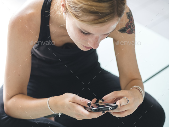 female friends in locker room of the gym relaxing looking at a smartphone and chatting - Stock Photo - Images