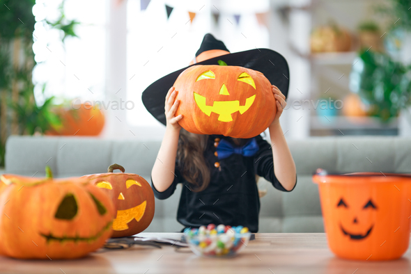 little laughing girl in witch costume - Stock Photo - Images