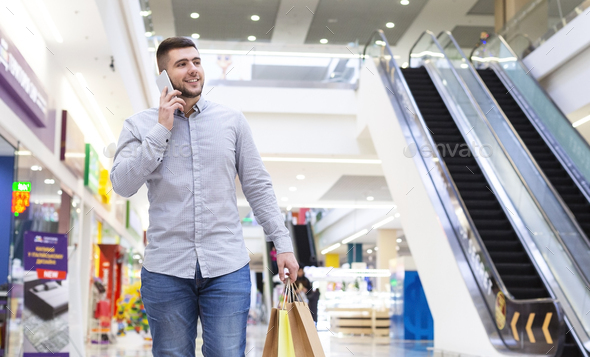 Young man with shopping bags talking by cellphone in mall - Stock Photo - Images