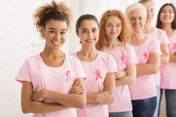Female Volunteers In Breast Cancer T-Shirts Standing Over White Wall - Stock Photo - Images