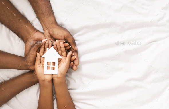 Closeup of paper house in hands of african american family - Stock Photo - Images