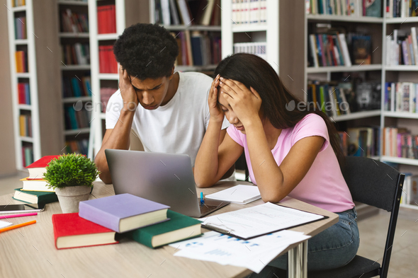 Exhausted black couple of students stucked with homework at library - Stock Photo - Images