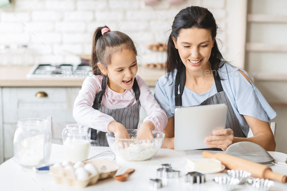 Mother and daughter using digital tablet in kitchen, looking recipe - Stock Photo - Images
