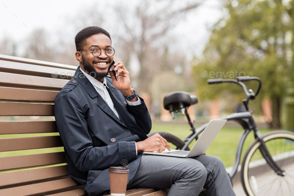 Handsome businessman having business talk during break in park - Stock Photo - Images