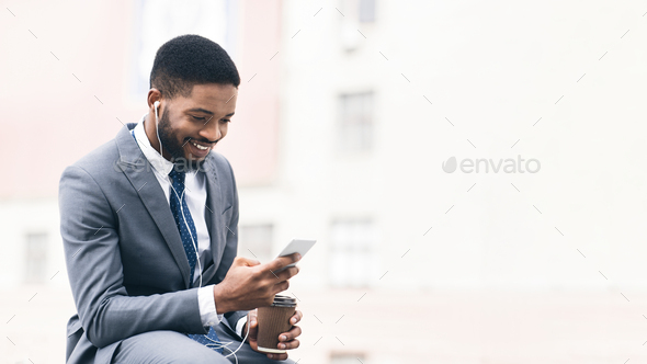 Businessman with coffee using cellphone near office - Stock Photo - Images
