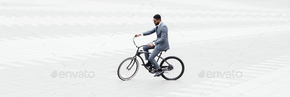Businessman riding bicycle to work in city center - Stock Photo - Images