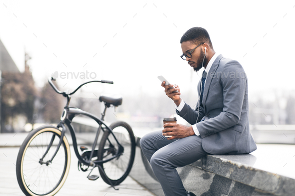 Afro businessman listening music and drinking coffee with bike nearby - Stock Photo - Images