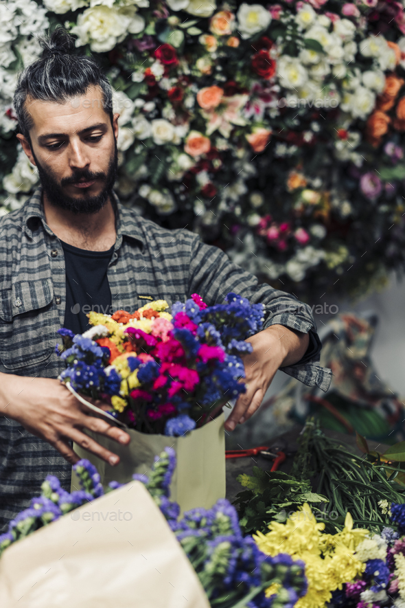 Young male florist working in flower shop - Stock Photo - Images