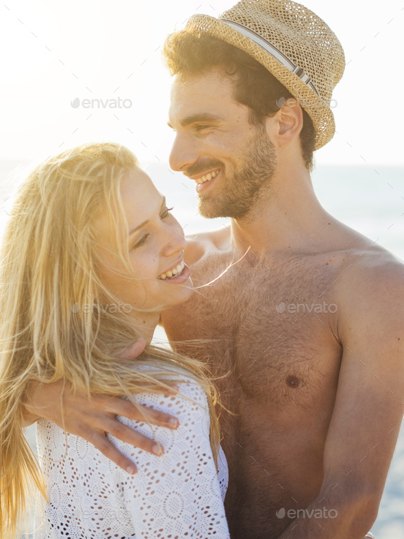 Young couple in love on a white beach at sunset - Stock Photo - Images