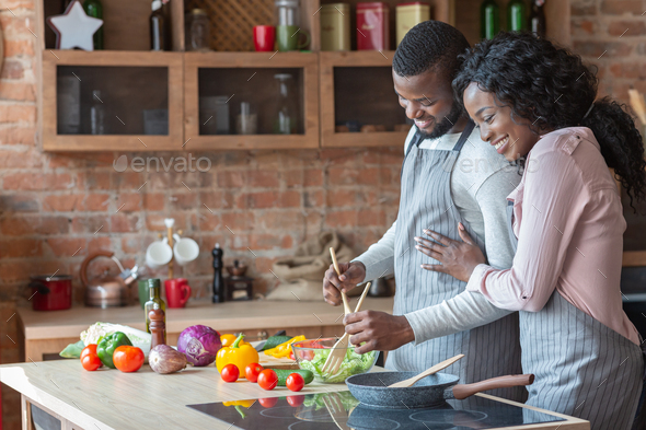 Cheerful black family cooking dinner together in kitchen - Stock Photo - Images
