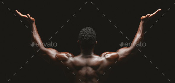 Rear view of african bodybuilder raising his palms up - Stock Photo - Images