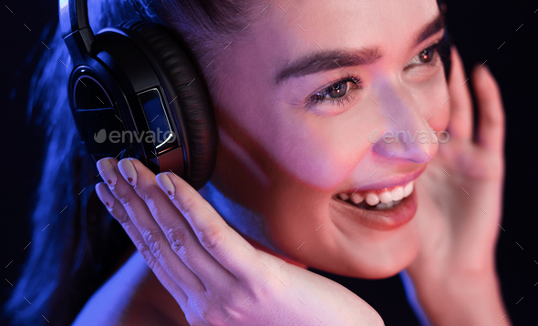 Young woman enjoying music in headset, posing in studio - Stock Photo - Images