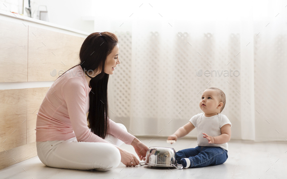 Little boy drumming with mother on metal saucepan at kitchen - Stock Photo - Images