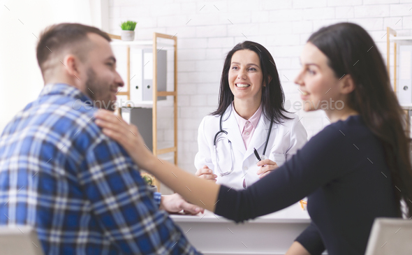 Happy wife supporting her husband after good news at hospital - Stock Photo - Images