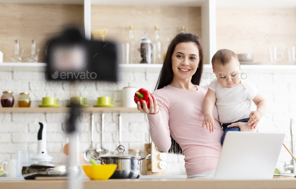 Young mother with little son shooting video about baby nutrition - Stock Photo - Images