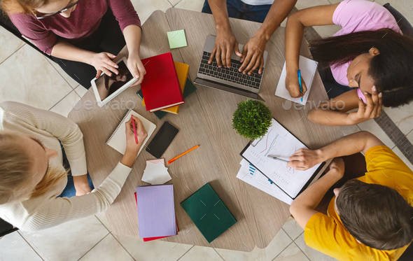 Group of international students sitting at table, top view - Stock Photo - Images