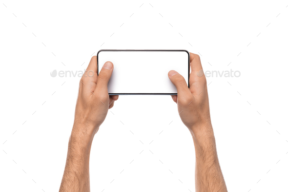 Male hands holding smartphone with blank screen, playing video games - Stock Photo - Images