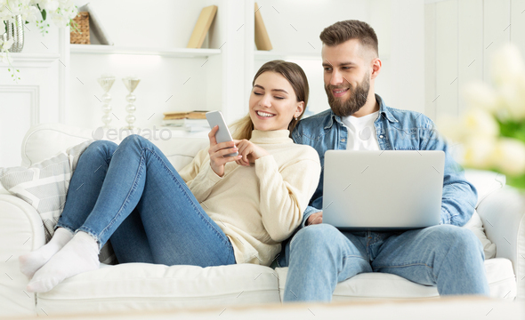 Millennial woman showing something on phone to husband - Stock Photo - Images