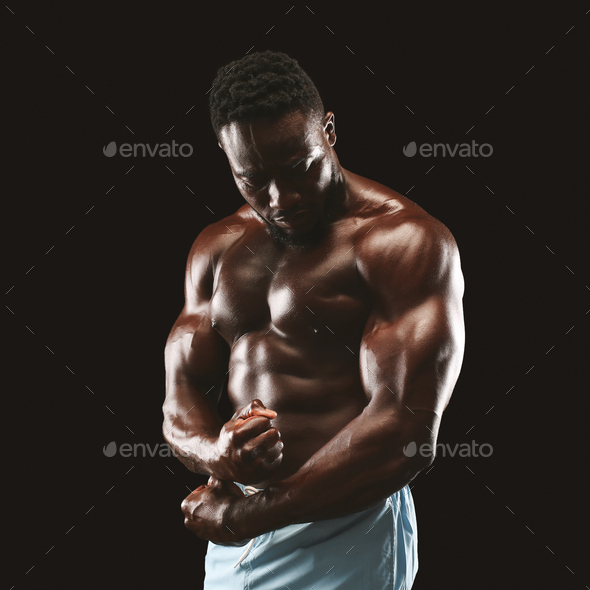 Portrait of black fitness model demonstrating side chest pose - Stock Photo - Images