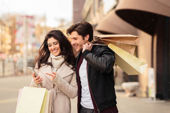 Order taxi online. Couple using smartphone after shopping - Stock Photo - Images