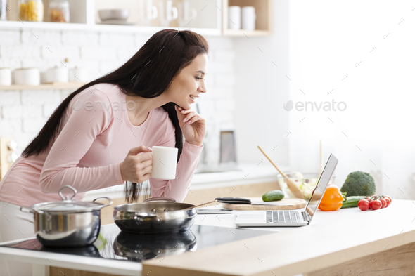 Millennial business woman working on laptop at kitchen - Stock Photo - Images