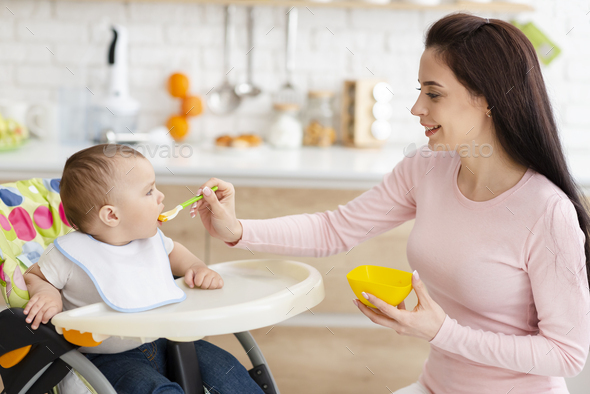 Mother feeding her baby, toddler sitting in high chair at kitchen - Stock Photo - Images