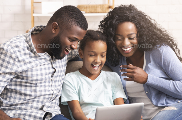 Black family watching funny videos on digital tablet at home - Stock Photo - Images
