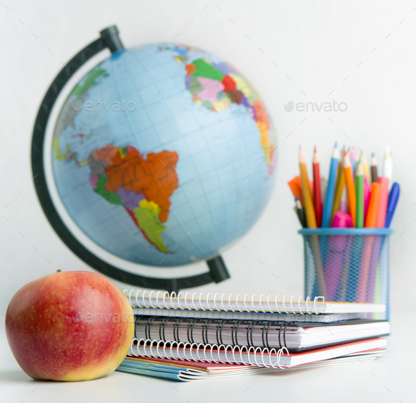 Close up of world globe and school stationery on white - Stock Photo - Images