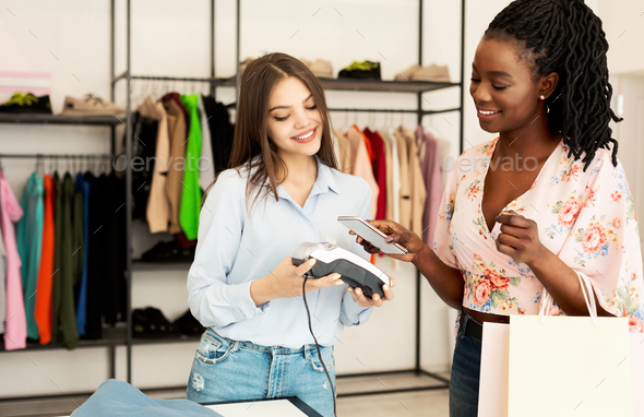 Happy Afro Girl Paying Via Cellphone In Fashion Boutique - Stock Photo - Images