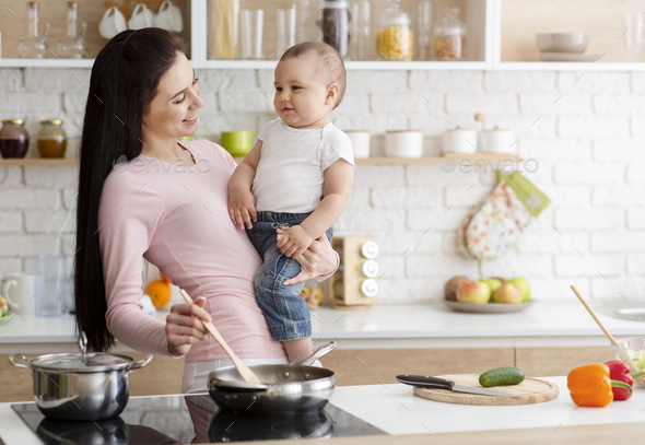 Mother cooking lunch with baby at kitchen - Stock Photo - Images