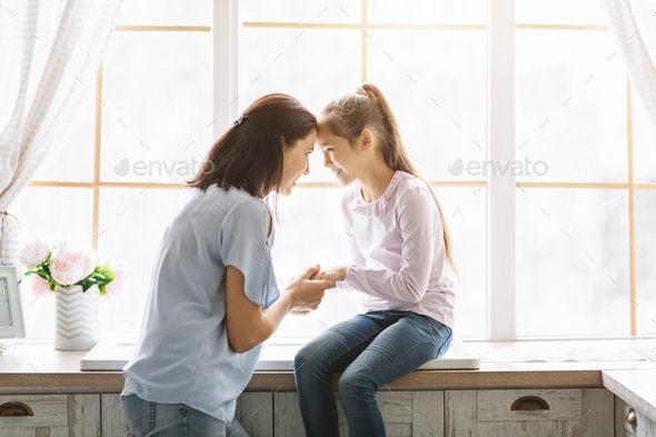Mother and daughter looking at each other and touching foreheads - Stock Photo - Images