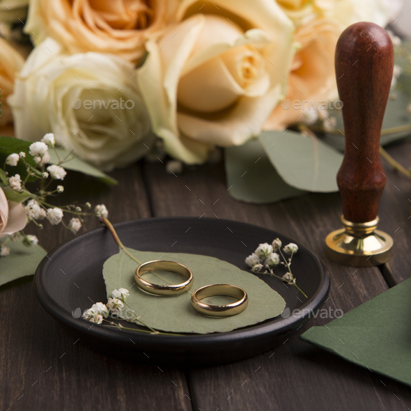 Close up of golden pair of wedding rings on plate - Stock Photo - Images