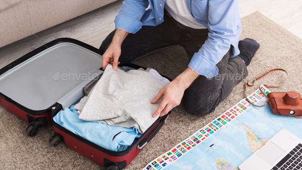 Man packing suitcase at home, sitting on floor - Stock Photo - Images